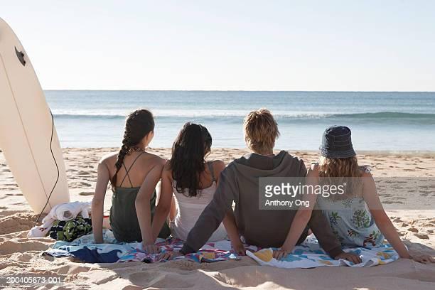 Teenage boy and three girls (15-18) sitting on beach, rear view