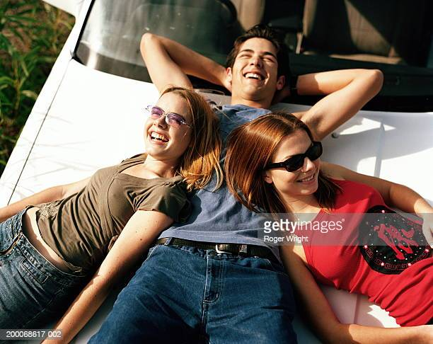 teenage boy and two teenage girls (15-19) lying on car bonnet - tinted sunglasses stock pictures, royalty-free photos & images
