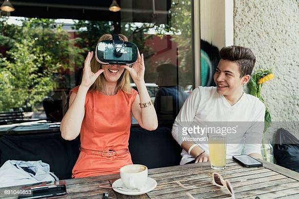 Teenage boy and woman wearing VR glasses
