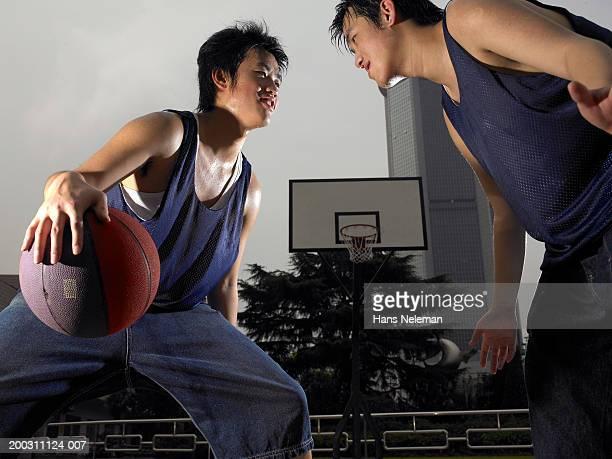 Teenage boy (17-19) and young man playing basketball