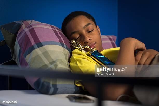 teenage boy asleep in bunkbed hugging trophy - teen awards stock-fotos und bilder