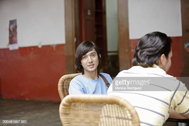 Teenage boy (17-19) at outdoor cafe