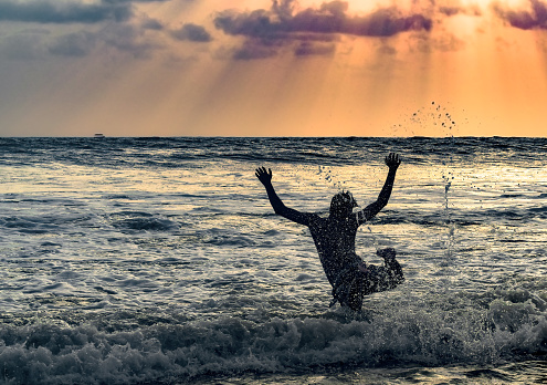 Teenage boy at vacation, having fun and celebrating life on a beach. He is jumping freely to dive in sea waves with both his hands and legs up in air. Beautiful sunset in the background. 1141907581