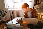 Teenage boy attending to online school class