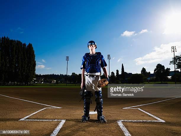 Teenage boy (13-14) baseball catcher at home plate, portrait