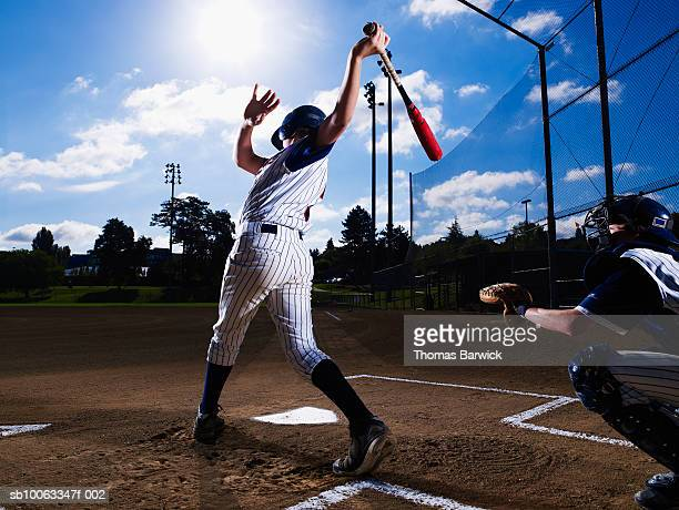 Teenage boy (13-14)  baseball player swinging bat, catcher behind him
