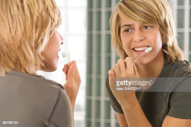 Teenage boy brushing his teeth