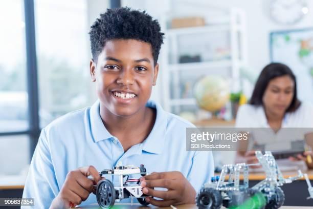Teenage boy builds robot model at school