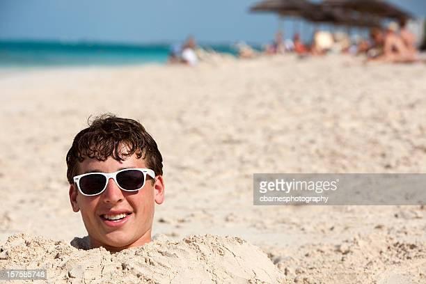 teenage boy buried in sand