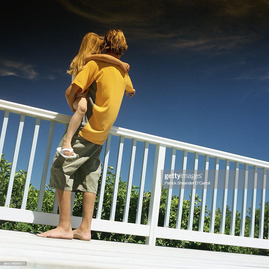 Teenage boy carrying girl, outside, rear view : Stockfoto