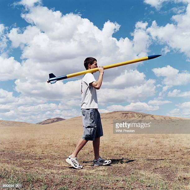 Teenage boy (17-19) carrying rocket over shoulder