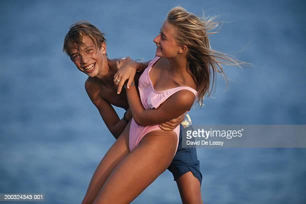 Teenage boy carrying teenage girl, laughing