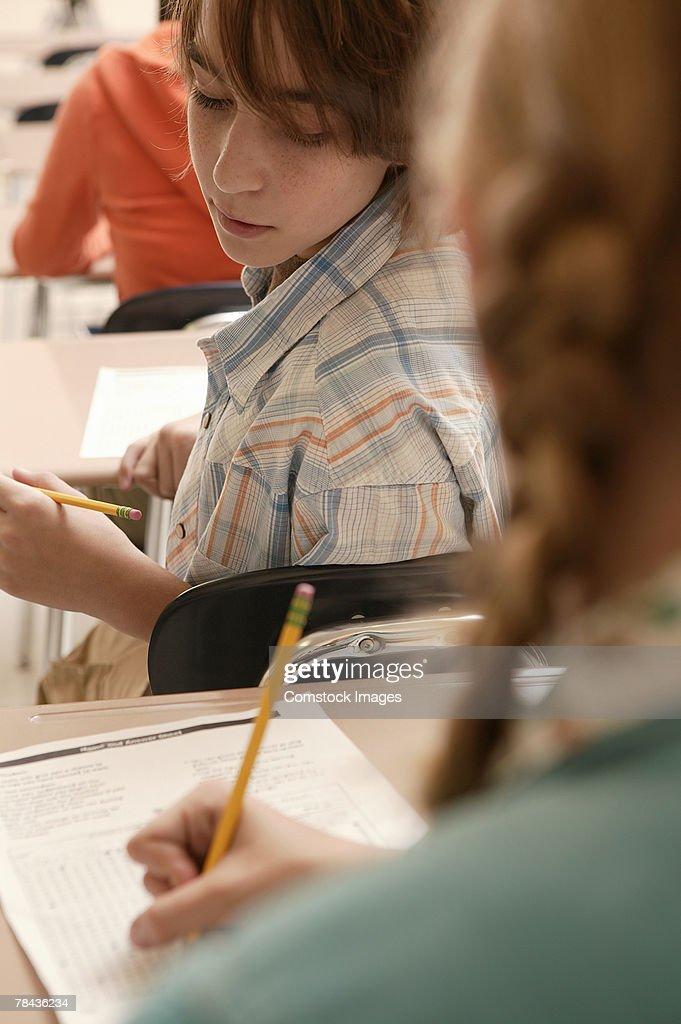 Teenage boy cheating in school : Stockfoto
