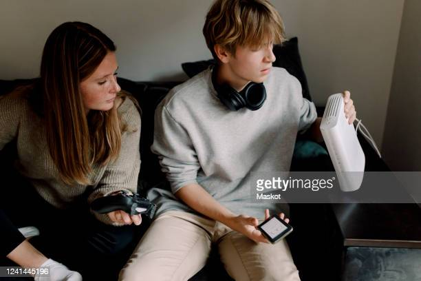 teenage boy checking wi-fi router while sitting with friend on sofa at home - stream stock pictures, royalty-free photos & images