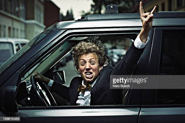 Teenage boy cheering while driving