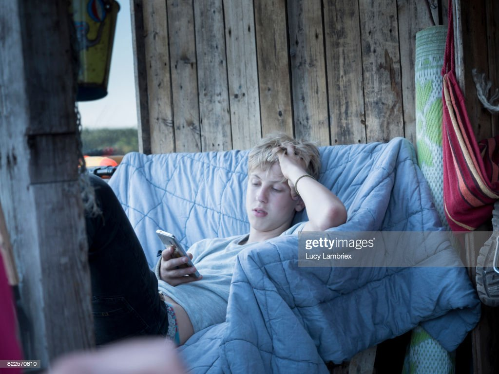 Teenage boy chilling with his smartphone : Stock Photo