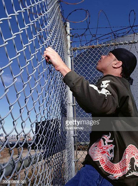 Teenage boy (16-17) climbing up wire mesh
