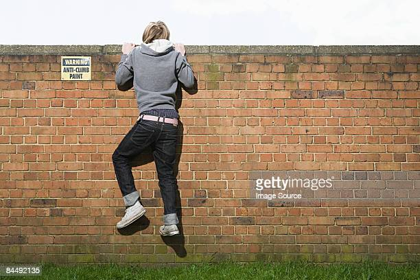 Teenage boy climbing wall