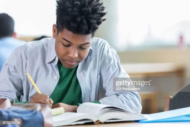 Teenager-Jungen konzentriert sich während seines Studiums in Bibliothek