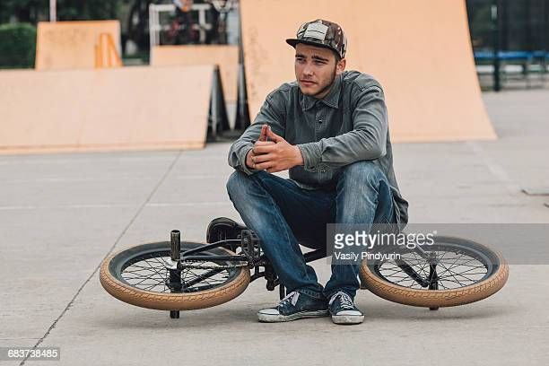 Teenage boy contemplating while sitting on bicycle at skateboard park