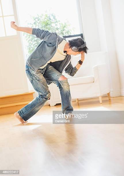 Teenage boy (16-17) dancing in living room