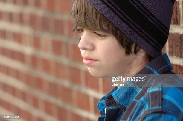 Teenage Boy Deep in Thought by Brick Wall