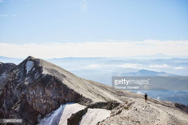 teenage boy descending on ridgeline from peak of mt st helens - moving up stock pictures, royalty-free photos & images
