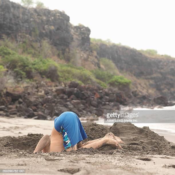 Teenage boy (12-14) digging hole on beach, sticking head in hole