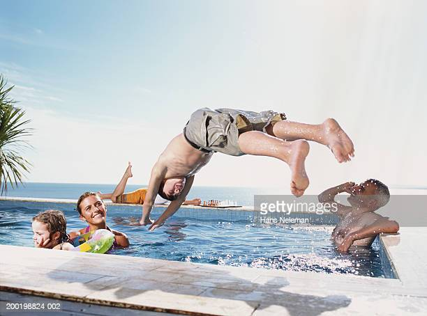 Teenage boy (13-15) diving into pool, family watching