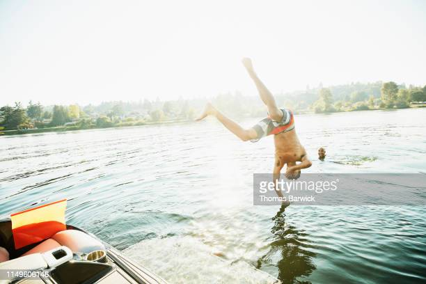 teenage boy diving off boat to swim with father on summer afternoon - naughty america stock pictures, royalty-free photos & images
