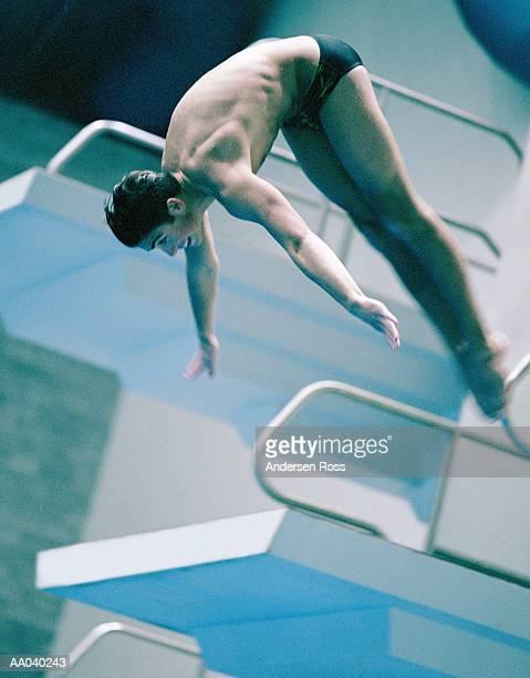 Teenage boy (16-18) diving off of platform (cross-processed)
