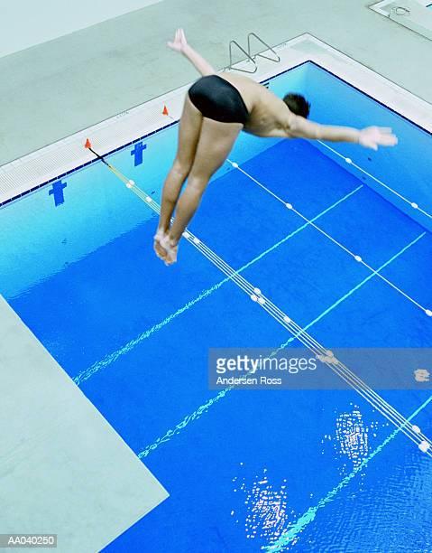 Teenage boy (16-18) diving off platform, elevated view
