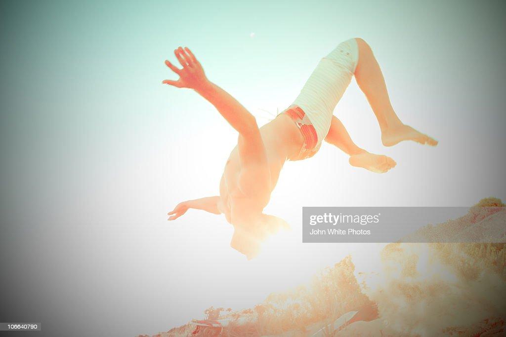 Teenage boy doing a back flip at beach : Bildbanksbilder