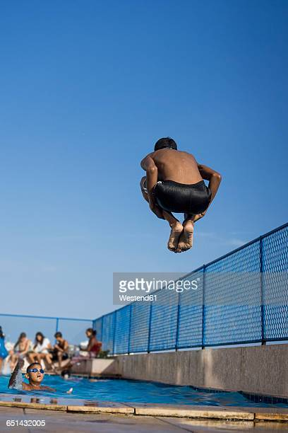 teenage boy doing a cannonball dive into swimming pool - キャノン ストックフォトと画像
