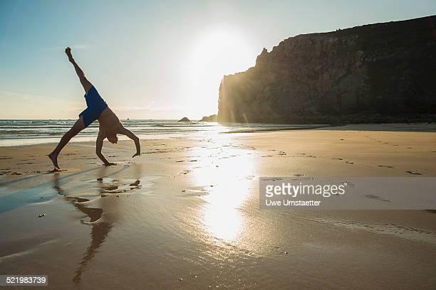 Teenage boy doing handstand on beach, Camaret-sur-mer, Brittany, France