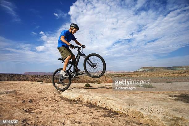 Teenage boy doing trick on bicycle