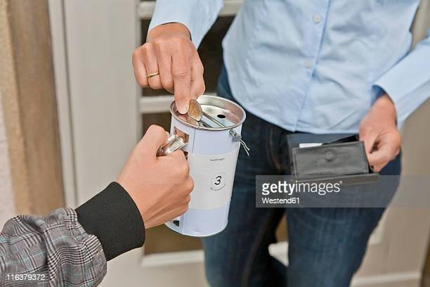 Teenage boy donating money at door