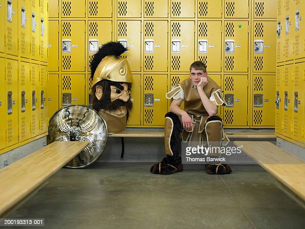 Teenage boy (15-17) dressed as mascot, seated in locker room, portrait
