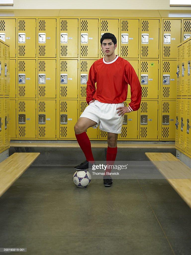 Teenage boy (16-18) dressed for soccer, standing in locker room : Stock Photo
