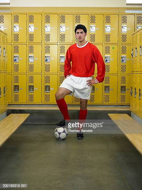 Teenage boy (16-18) dressed for soccer, standing in locker room