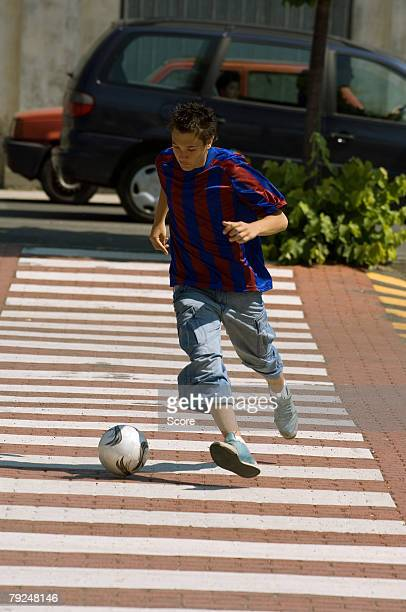 teenage boy dribbling soccer ball in town - zebra crossing stock pictures, royalty-free photos & images
