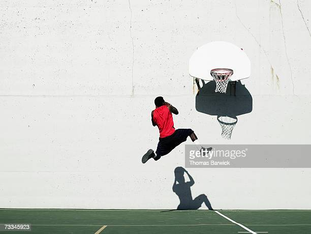 Teenage boy (16-18) dunking basketball on outdoor court, mid-air, rear view