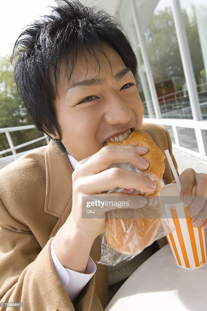 Teenage boy eating bread and holding disposable cup at terrace : Photo