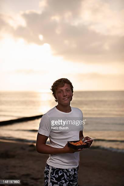 Teenager junge Essen am Strand