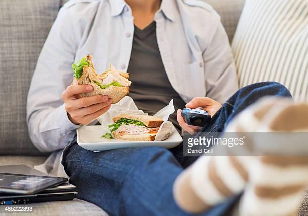 Teenage boy(16-17) eating sandwich and watching tv