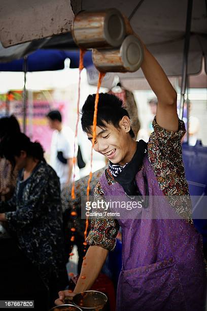 CONTENT] A teenage boy elaborately pulls Thai style milk tea at a stall in Bangkok's Chatuchak weekend market