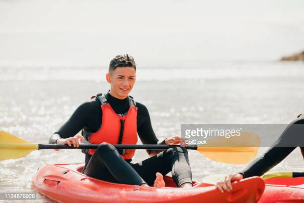 teenage boy enjoying time kayaking - kayak stock pictures, royalty-free photos & images
