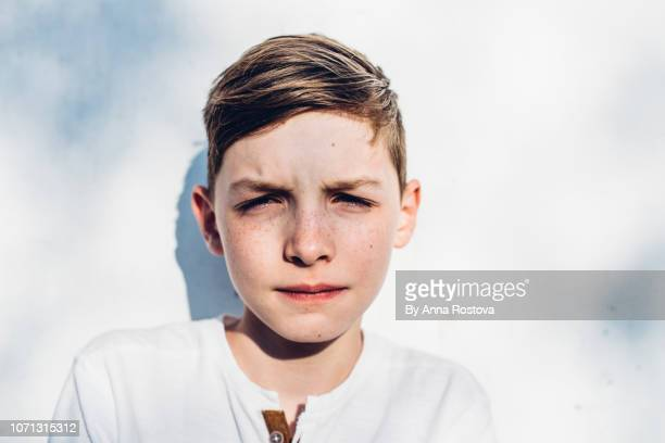 teenage boy eyes narrowed against bright sun - squinting stock photos and pictures