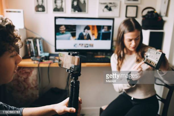 teenage boy filming friend using sound mixer on monopod while sitting at home - メディア機材 ストックフォトと画像