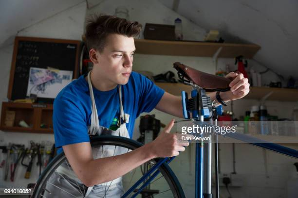 Teenage boy fixing bicycle in shed